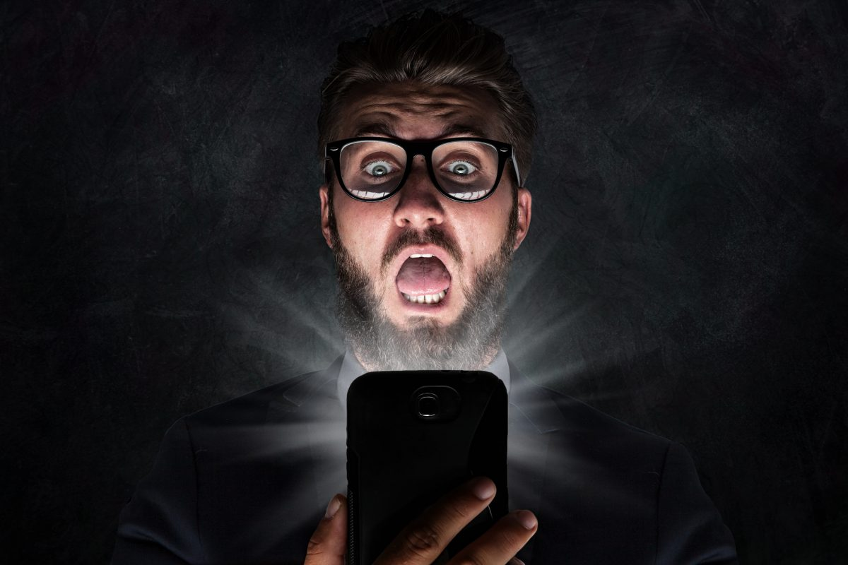 Nerd with glasses is shocked after reading news on his phone